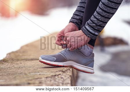 Cropped shot of male runner tying his shoelaces before running workout outdoors in winter