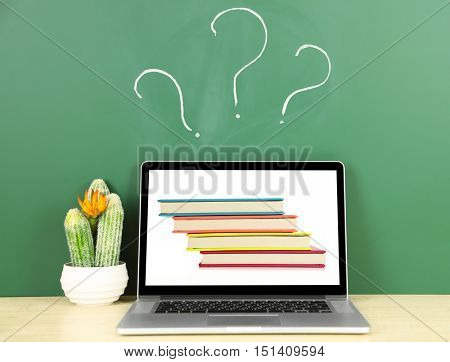 Laptop with stack of notebooks wallpaper on screen against chalkboard. Question mark on background. School teacher concept.