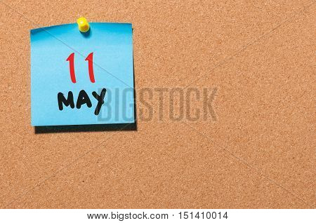 May 11th. Day 11 of month, calendar on cork notice board, business background. Spring time, empty space for text.