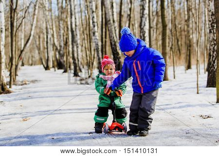 little brother helping sister to ride scooter in winter, kids friendship and learning