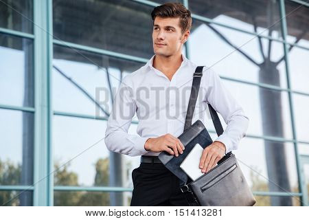Handsome young businessman taking pc tablet from his bag while standing near business center