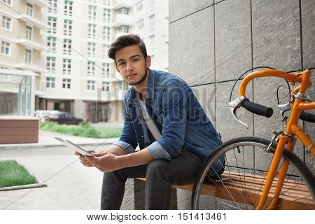 Guy in denim jacket with beard and orange bicycle sitting on a bench holding a tablet looking at the camera on the background of buildings