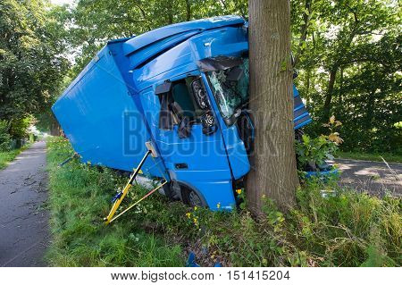 A truck crashed against a tree on a small road outside the city.