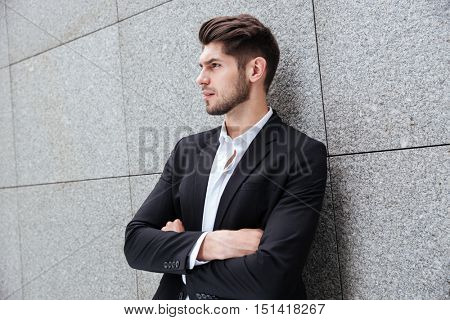 Profile of serious young businessman standing with arms crossed