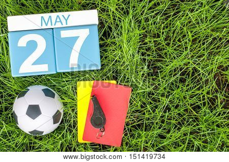 May 27th. Day 27 of month, calendar on football green grass background. Spring time, empty space for text.