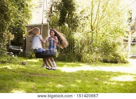 Two Girls Playing Together On Tire Swing In Garden