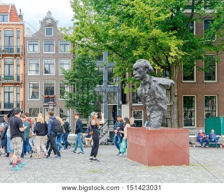 Amsterdam, The Netherlands - August 29, 2016: Tourists around the statue of Dutch writer Eduard Douwes Dekker, better known under the pseudonym Multatuli, on the bridge over the Singel in Amsterdam.