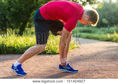 Sprinter starting sprint - man running getting ready to start sprinting run. Fit male runner athlete training outside on road in beautiful mountain landscape nature