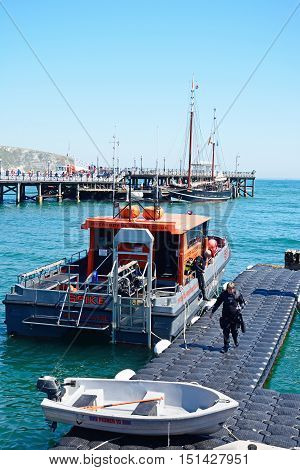 SWANAGE, UNITED KINGDOM - JULY 19, 2016 - Dive boat moored alongside a pontoon with the pier to the rear Swanage Dorset England UK Western Europe, July 19, 2016.