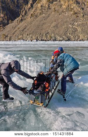 Lake Baikal, Russia, March 24. The Men Dragged The Ice Sledge Through A Crack In The Ice Of Lake Bai