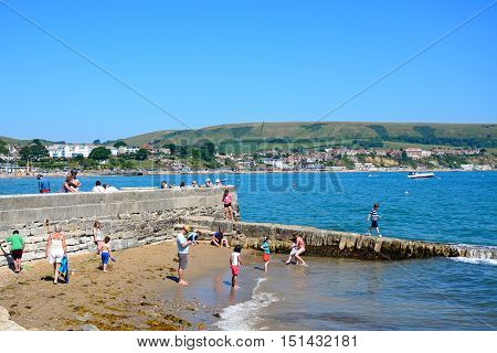 SWANAGE, UNITED KINGDOM - JULY 19, 2016 - Holidaymakers on the beach by the harbour wall with town buildings to the rear Swanage Dorset England UK Western Europe, July 19, 2016.