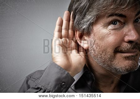 Hand and ear of eavesdropping listening man.