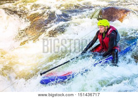 The Man Supsurfing On The Rapids Of The Mountain River