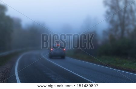 Car With Red Stoplights On Foggy Highway
