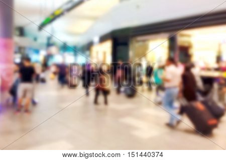 Blurred people in the shopping mall airport with wheel luggage