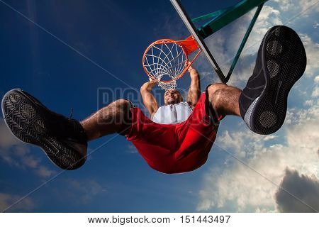Low Angle View of Man Hanging on Basketball Hoop
