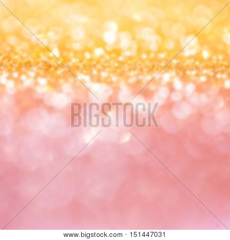 Defocused Bokeh twinkling lights - golden and pink twinkle lights. Festive blur sparkling background.