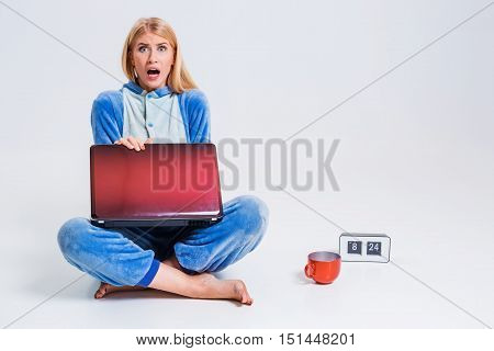 young woman sitting on the floor in his pajamas with a laptop. Working or studying in the morning after sleep. surprised, frustrated, incredulous, looking at the camera