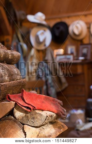 Working gloves rest on a woodpile in a rustic home with a collection of cowboy hats in the background.