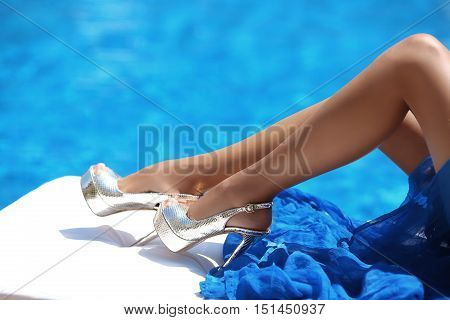 Close Up Sexy Tanned Long Legs In High Heels Lying On Deck Chair Against The Swimming Pool With Blue