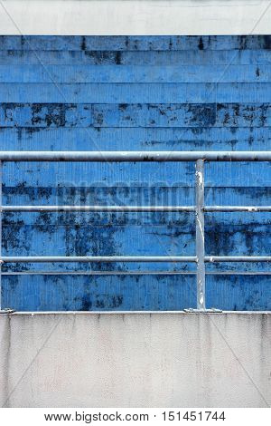 Blue concrete bleachers steps and railing in vertical 3:2 format.