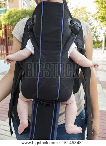 A Mother Carries Her Baby With A Black Front Pack