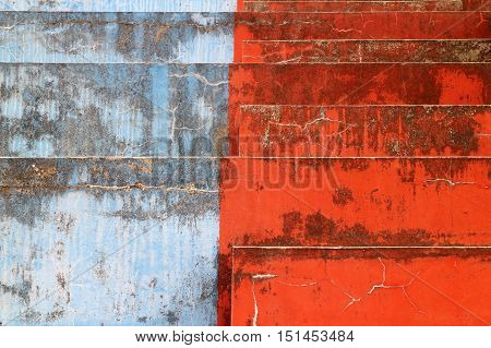 Blue and red bleachers steps with weathered patina.