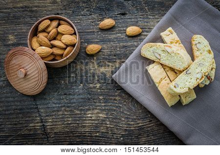 Italian cantuccini cookies with almonds. Traditional italian almond cookies biscotti on wooden background. Homemade Almond cookies with space for text on wooden table. Top view. Copy space.