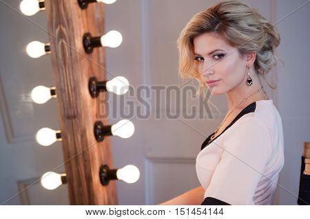Beauty luxury blonde woman with and mirror. Attractive young woman in beautiful dress sitting in front of a large mirror, to primp