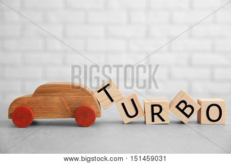 Cubes with word TURBO and toy car on brick wall background