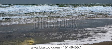 coastal beach scenery including waves and spume