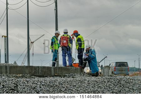 Tobolsk, Russia - July 15. 2016: Sibur company. Construction of plant on processing of hydrocarbons. Surveyor builders worker with theodolite transit equipment at construction site outdoors during surveying work