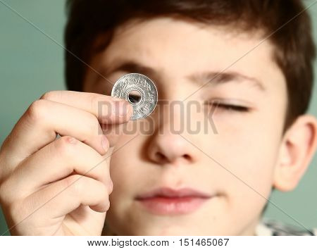 boy preteen numismatic collectioner show his coin with hole in the middle look through it close up portrait