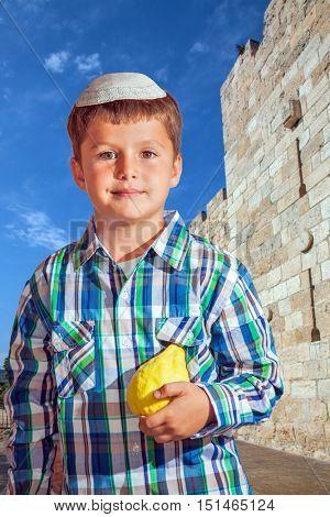 Sukkot in Jerusalem. Charming seven year old boy in white silk skullcap with etrog