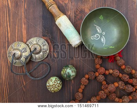 Tibetan singing bowl and objects for religious ritual on a brown wooden background top view