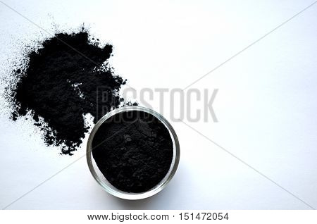 Powdered activated charcoal in a glass bowl, top view, on white background, with copy space