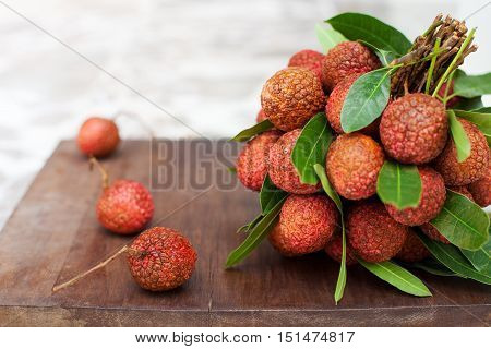 Lychee with leaves on a wooden board, still life Copy space