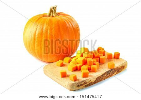 Sliced cubes over wooden board and whole pumpkin isolated on white baskground