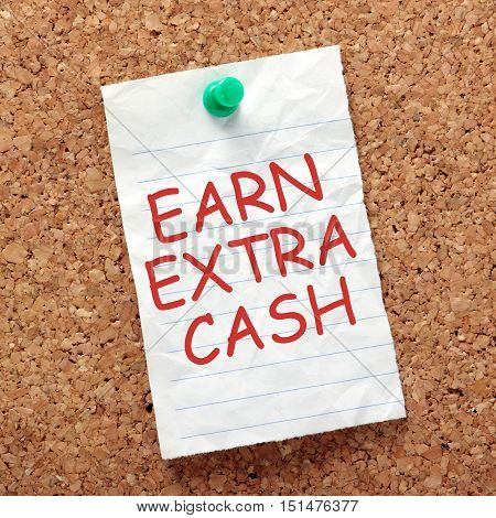 The words Earn Extra Cash in red text on a piece of lined paper pinned to a cork notice board as a reminder to find ways to make more money on the side