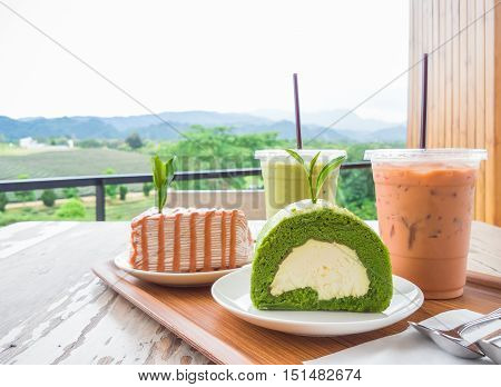 Thai iced milk tea, Thai milk tea crepe cake, iced matcha green tea, matcha green tea roll cake on a wooden tray and table at the bakery shop located in tea plantation surrounded by beautiful valley.