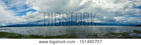 Panoramic beautiful view with the blue sky, white cloud and mountain of Kwan Phayao that is located in Phayao, Thailand. Many water hyacinth come with plenty of water after several days raining.