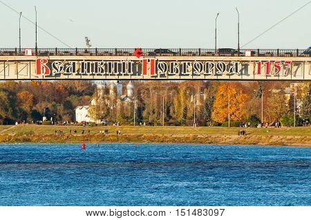 VELIKY NOVGOROD RUSSIA - OCTOBER 9 2016. Road bridge across the Volkhov river in Veliky Novgorod Russia with the inscription Veliky Novgorod 1157 - autumn city landscape at the sunset