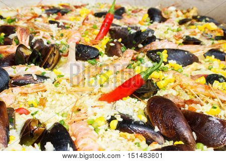 Cooked mussels with rice and greens. Background pattern of rice. Delicatessen mollusks on street food festival.