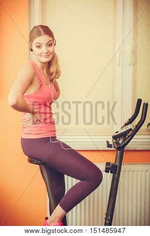 Active young woman working out on exercise bike stationary bicycle. Sporty girl training at home listening music. Fitness and weight loss concept.