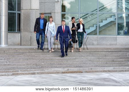 five business people (two man and three woman) descend steps from center of business