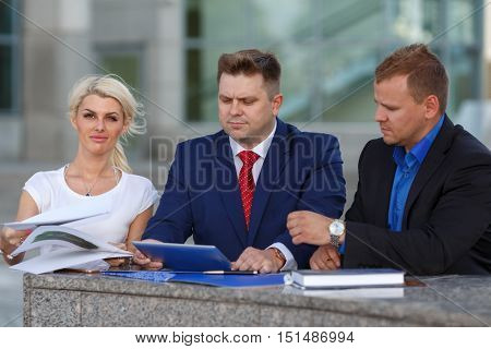 Image of friendly business team, two man and woman, discuss project, man in tie looks at tablet