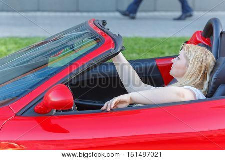 Portrait of young woman sitting behind wheel driving red luxury roadster