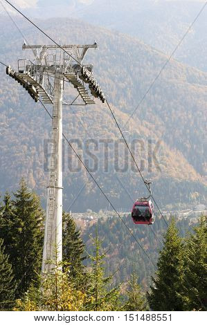 Cableway in Romanian Carpathians during summertime with passenger cabin moving. Focus at cabin, slightly blurred background