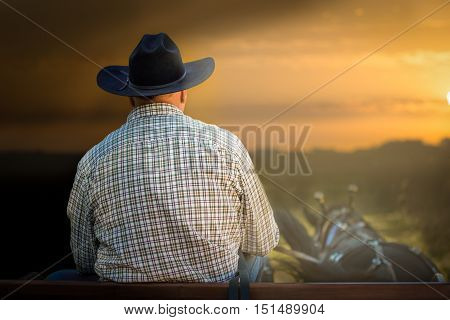 Cowboy riding a horse driven wagon, in a beautiful sunset out in country or desert.
