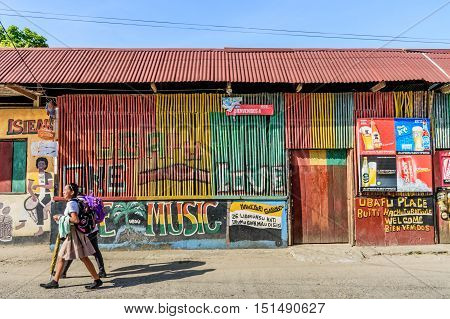 Livingston Guatemala - August 31 2016: Girls walk past colorfully painted walls in street in Caribbean town of Livingston